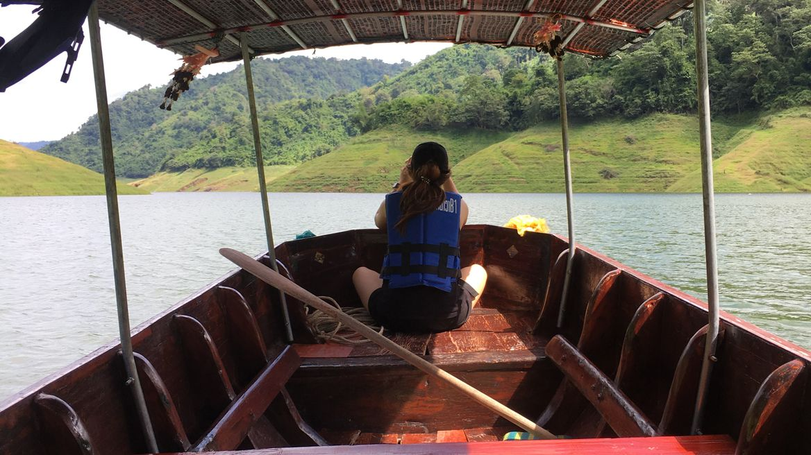 Long tail boat ride through the vast surface of water inside the dam with cool breeze air flowing through your hair